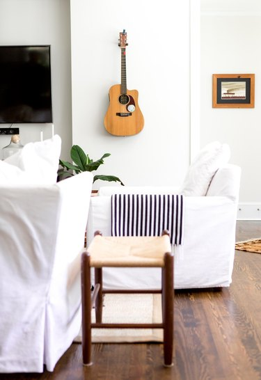white bohemian living room idea with hanging guitar