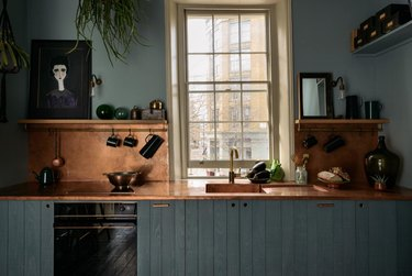 Rustic colors in kitchen with muted teal cabinets, copper counters and backsplash, open shelves, cream trim on window.