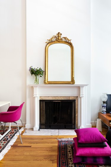 white traditional fireplace with gold mirror on the mantel