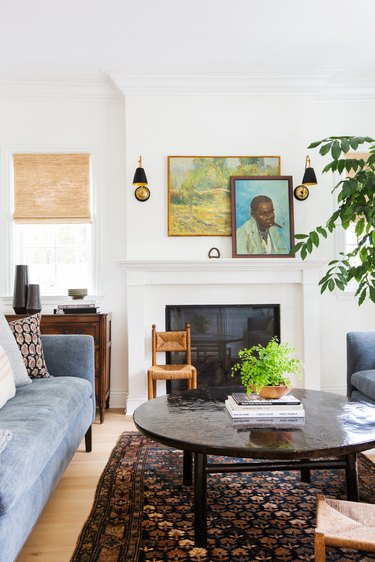 white living room with white traditional fireplace and coffee table with art on the mantel