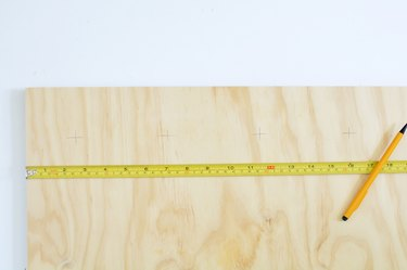 Measuring plywood with yellow tape measure