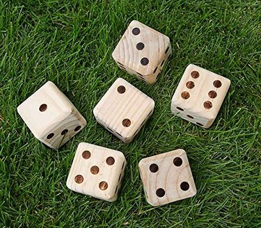 Large wooden dice in grass