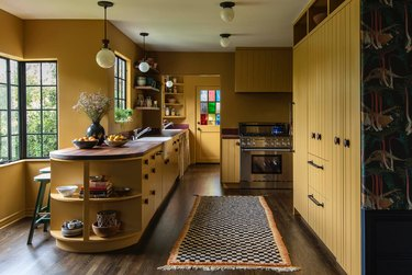 Kitchen with mustard yellow cabinets, dark wood floors, island with open curved shelves, wood counters, runner rug, stainless stove with rustic colors
