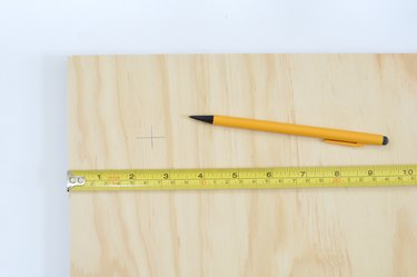 Plywood sheet with tape measure and pencil