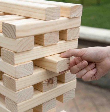 A hand removes a large wooden brick from a stack