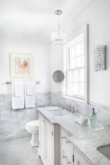 White bathroom with coastal theme and wainscoting
