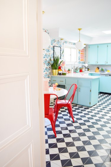 retro colorful maximalist kitchen with blue cabinets and checkerboard flooring
