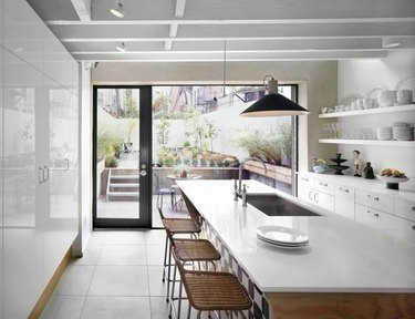 Floor-to-ceiling kitchen windows in modern kitchen with wood and white island and woven bar stools