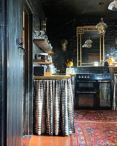 maximalist kitchen with dark walls and skirted cabinets
