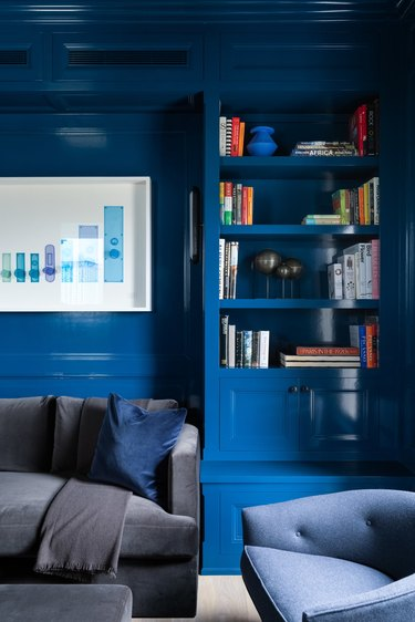 room with blue paint color on walls and bookcase