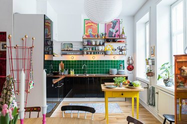colorful maximalist kitchen with green tile backsplash and black cabinets