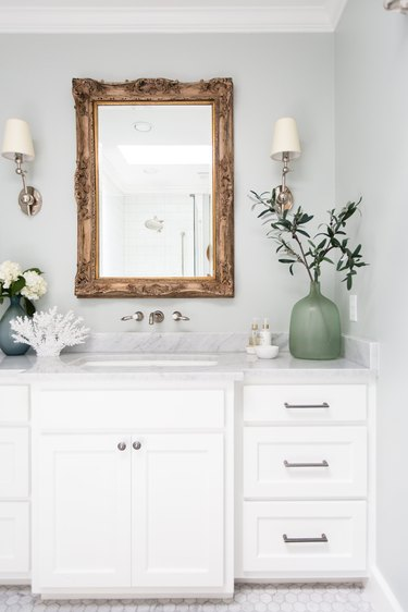 light blue paint color bathroom with white vanity and mirror