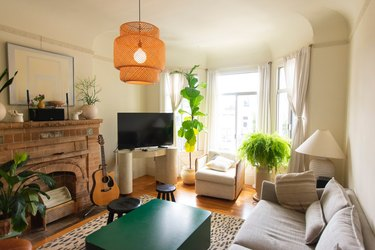 Living room with exposed brick fire place, plants, and bay window curtains