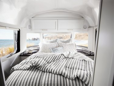 airstream with bed with striped sheets