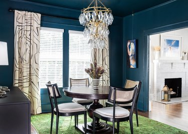 dark blue paint color in dining room with table and beige window treatments