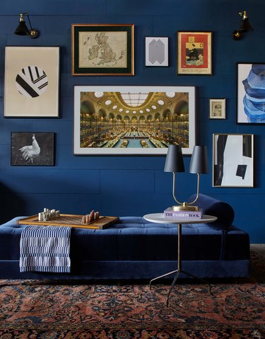 blue living room wall with gallery wall and daybed