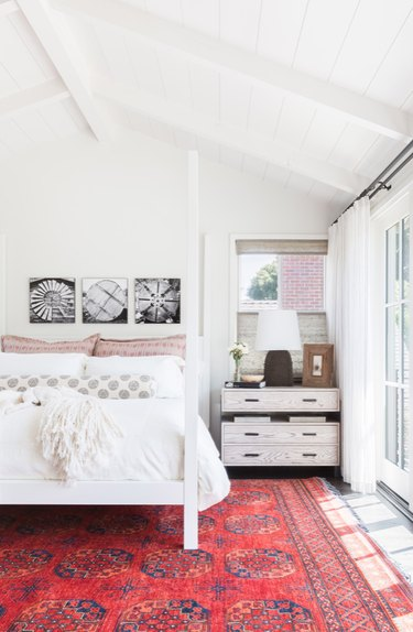 White arch ceiling bedroom and white bedding with vermillion color area rug.