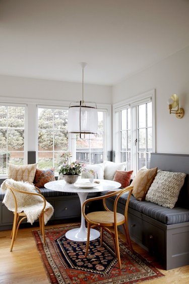 white kitchen with gray linen window bench and small table