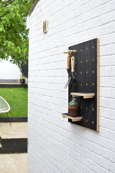 Painted black wooden pegboard with garden tools