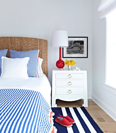 Blue and white striped shams and duvet, wicker headboard, and vermillion color table lamp with white shade, white night stand, black and white photograph, dark blue and white striped area rug, red shoes.