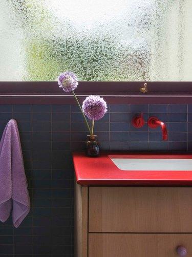vermillion color counter, red faucet, purple window trim, towel and flowers, blue tile.