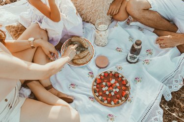 overhead shot of people having a picnic on a blanket