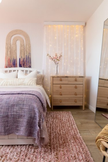 Pink and purple bedroom with fairy lights on wall and modern wall tapestry