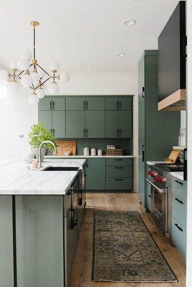 Forest green kitchen colors in kitchen with vintage runner and modern chandelier