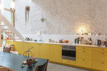 Yellow kitchen colors in kitchen with white brick walls