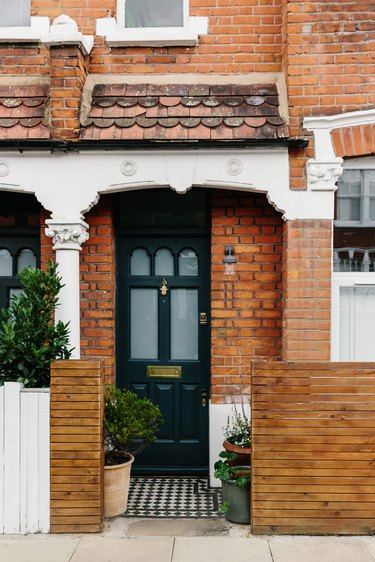 traditional brick home with white trim and potted plants at black front door