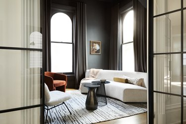black windows in living room with burnt orange chair and white couch