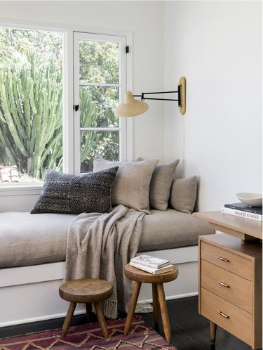 white room with gray window bench and two stools below it
