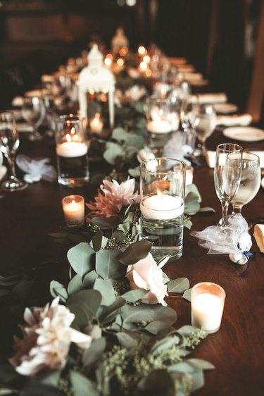 country table setting with candles, lanterns and fresh flowers