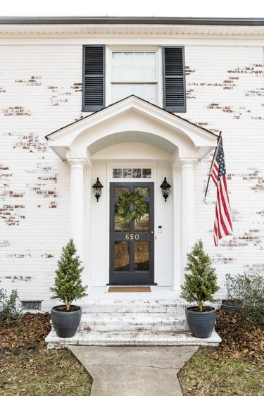 Traditional brick home in limewash paint with American flag