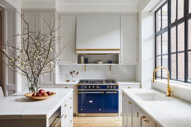 black windows in white kitchen with blue stove and white range hood