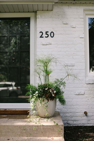 Traditional brick home painted white and featuring midcentury house numbers