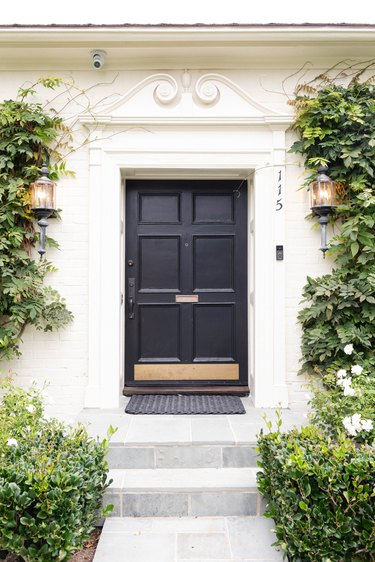 black traditional front doors with brass kick plate