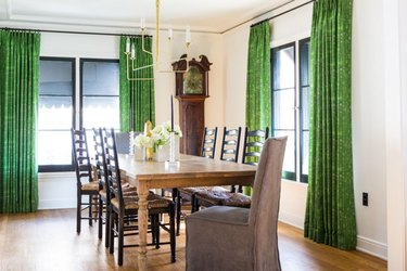 black windows in dining room with wood floors and green window treatments