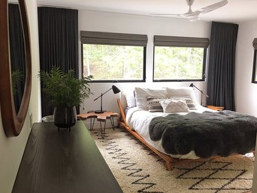 black windows in bedroom with geometric pattern rug, platform bed, and tree stump bedside table