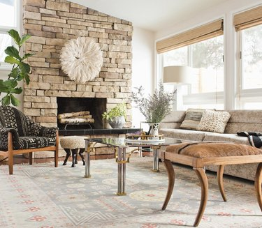 vintage living room idea with eclectic vintage living room with two stools, a glass coffee table, a beige couch, and an armchair covered in mudcloth