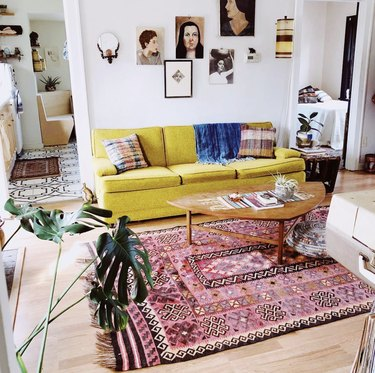 vintage living room idea with a pink patterned rug and light green couch