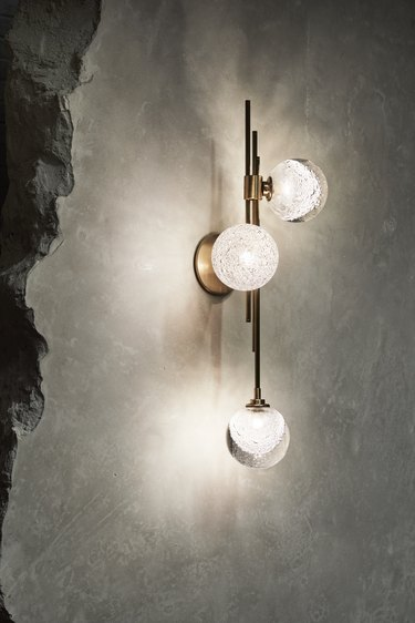 brass wall sconce with glass shades on concrete wall