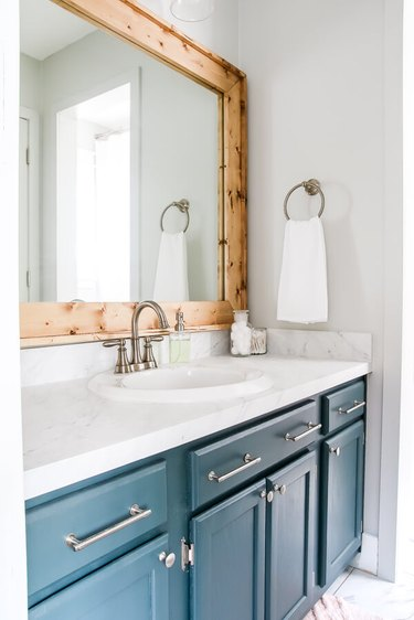 white bathroom with blue vanity and diy rustic decor wood frame mirro