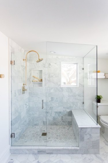Marble bathroom shower idea with built-in bench and window