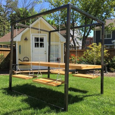 swing table and chairs on grass near a yellow house