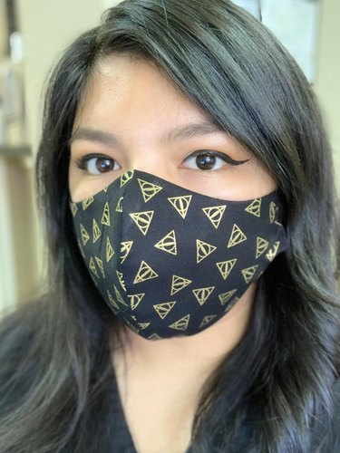 person wearing mask with deathly hallows pattern