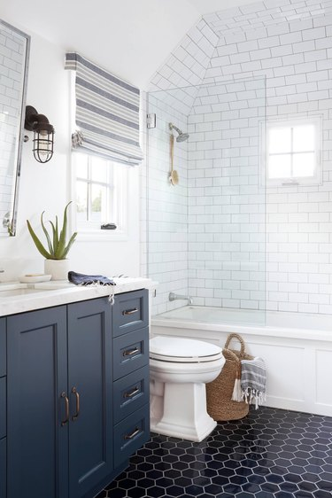 dark bathroom floor tile idea with blue vanity cabinet and subway tile walls in shower