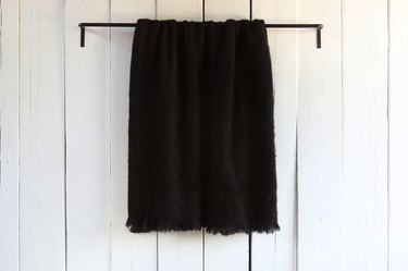 Black mohair throw hanging on wall