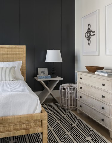 Coastal black bedroom idea with woven rattan bed and area rug