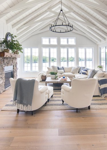 coastal living room white arched ceiling with white beams, iron chandelier, stone fireplace, light oak floors, white wing back chairs, white sectional.